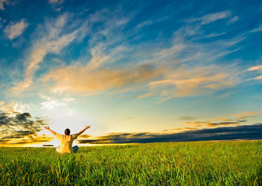 man sitting in the field under sunset